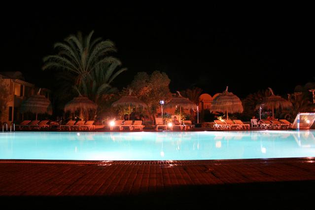 noční bazén s lehátky a lidmi na dovolené.jpg